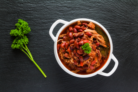 Beans with pork stewed in spicy tomato sauce with onion, paprika, beer, bell and pink pepper. White soup bowl and fresh parsley on black stone, top view.