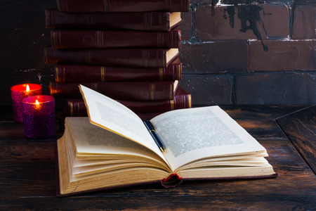 Old vintage books laying like a tower on a dark wooden table and one open book. Red hard cover, burning candle flames.