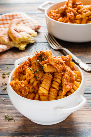 Fusilli pasta with chicken. Cooked in spicy sauce from tomatoes, onion, garlic, dried oregano and thyme, paprika and olive oil. Fresh bread, white bowl and casserole on wooden brown rustic table. Zdjęcie Seryjne