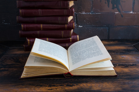 A stack of books with a dark red hard cover one another and open book on a wooden table against the background of brown brick wall behind.