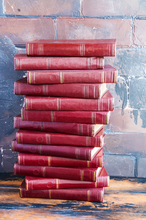 A stack of books with a dark red hard cover one another on a wooden table against the background of brown brick wall behind. Stock Photo
