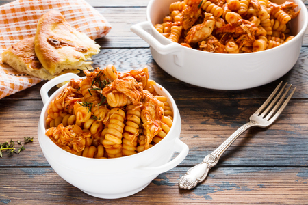 Fusilli pasta with chicken. Cooked in spicy sauce from tomatoes, onion, garlic, dried oregano and thyme, paprika and olive oil. Fresh bread, white bowl and casserole on wooden brown rustic table. Stock Photo