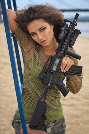 Girl with a rifle on the beach photo