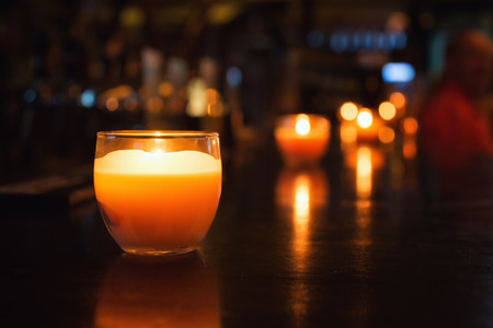 Candle in a glass. Photos of cafe or restaurant reception. Selective focus with bokeh.