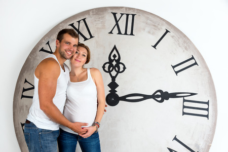 Happy Pregnant Couple on white background with giant clock. photo