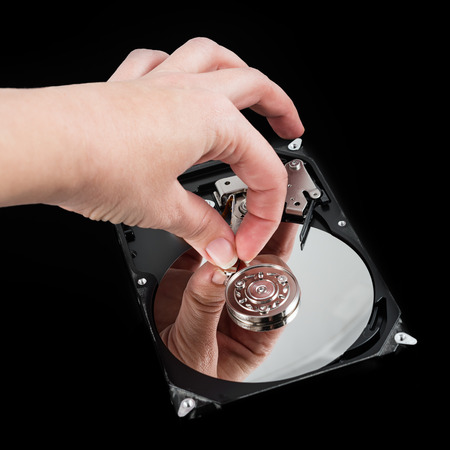 hard drive crash: Opened external hard drive. Female hand touching disk. Data loss concept, computer crash Stock Photo