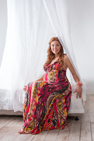 Young beautiful fashion pregnant woman in colorful dress sitting on a bed with a canopy on a white background.