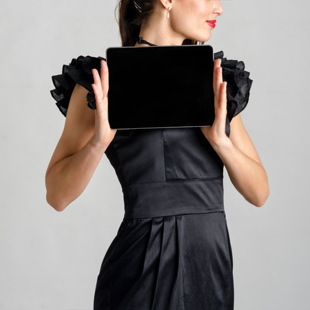 Business woman holding and shows touch screen tablet pc with blank screen. photo