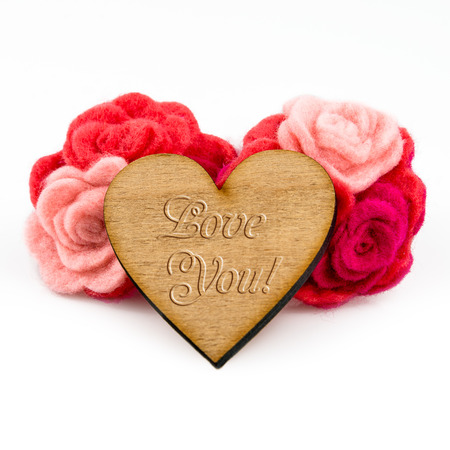 Wooden heart with carved words and red wool flowers on white background. Valentines Day greeting card photo