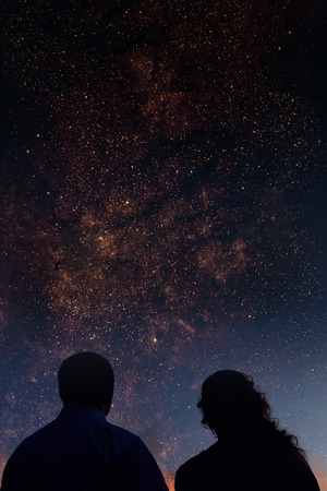 Silhouettes of couple looking at stars. Starry night sky with colorful galaxies, astronomical background with place for your text.