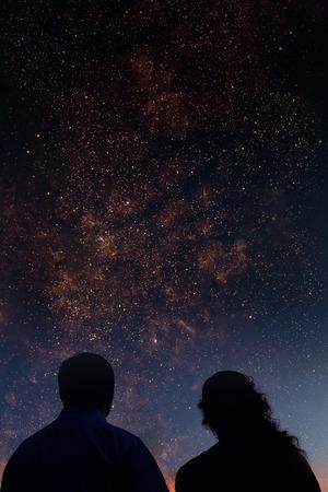personas mirando: Siluetas de pareja mirando las estrellas. Cielo de la noche estrellada con galaxias coloridas, fondo astron�mica con lugar para el texto. Foto de archivo