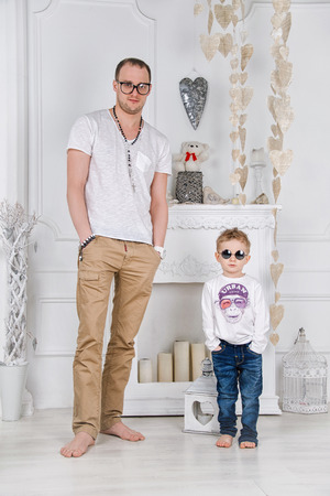 alike: Father and son in white living room with a fireplace. Mens fashion