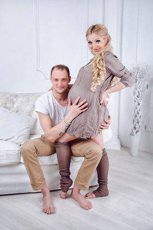 gestation: Happy young pregnant couple embrace each other on a sofa in white living room. Stock Photo