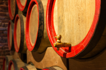 maturing: Wine barrels in the antique cellar. Cavernous wine cellar with stacked oak barrels for maturing red wine. Selective focus