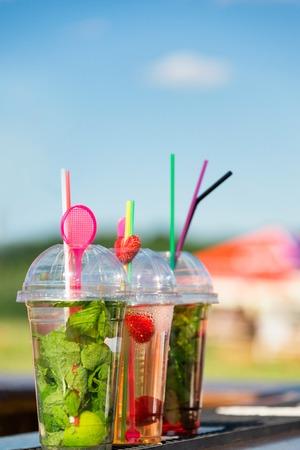 cocteles de frutas: Cócteles de frutas frescas en vasos de plástico listos para beber. Calle festival de comida, foto al aire libre Foto de archivo
