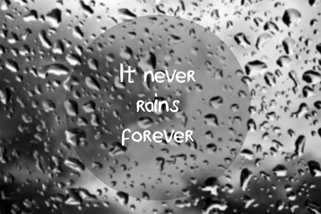 rain window: Inspirational quote with words It never rains forever on blurred natural background with water drops on window glass texture Stock Photo