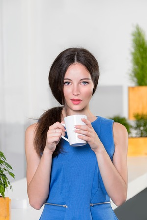 lovely businesswoman: Young businesswoman holding a cup off coffee. Beautiful girl drinking coffee or tea in cafe. Lovely young woman with the cup of hot beverage looking at camera