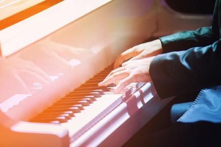 piano closeup: Mans hands playing piano closeup.