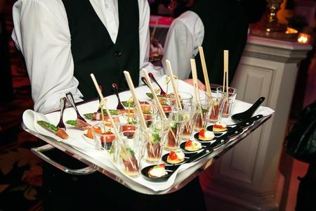 charolas: Servidor que sostiene una bandeja de aperitivos en un banquete