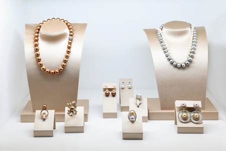 Set of luxury jewelry with precious gems and diamonds. Necklaces made of natural pearls on a stands. Women accessories