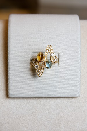 ring stand: Luxury ring made of yellow gold with diamonds and precious colorful gems on a stand