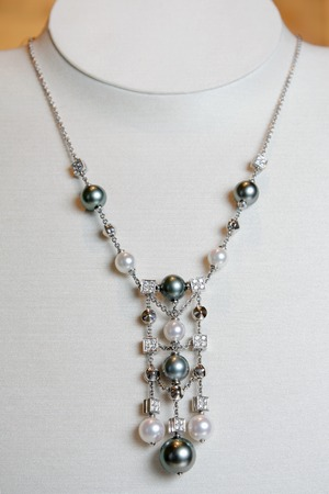 perls: Luxury necklace made of white gold with diamonds and perls on a stand Stock Photo