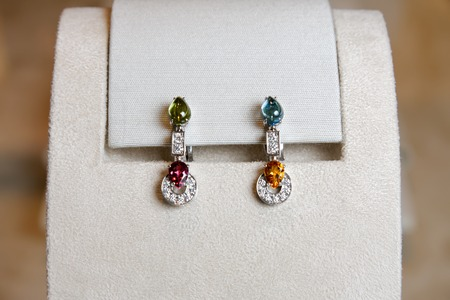 white gold: Luxury earrings made of white gold with diamonds and precious colorful gems on a stand.