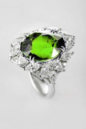 emerald: White gold or silver ring with diamonds and green emerald gemstone on gray background. Selective focus