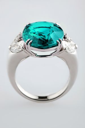 zircon: White gold or silver ring with blue sapphire or zircon gemstone on gray background. Selective focus