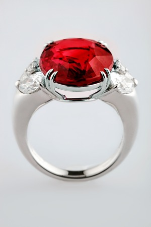 ruby gemstone: White gold or silver ring with red ruby gemstone on gray background. Selective focus Stock Photo