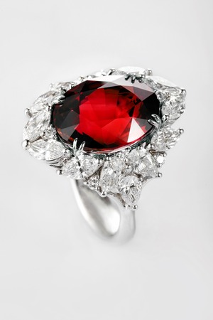 ruby gemstone: White gold or silver ring with diamonds and red ruby gemstone on gray background. Selective focus Stock Photo