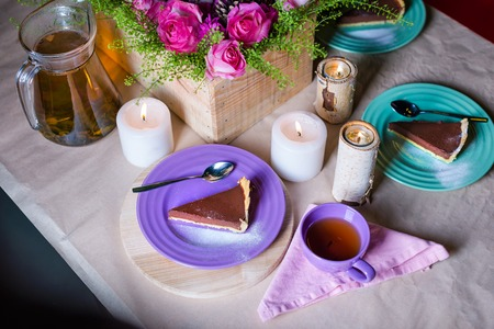 cake plate: Piece of delicious chocolate mousse cake on colorful plate on wooden table background. Table setting with flowers and candles for tea party. Selective focus