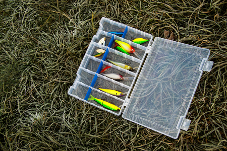 tackle: Set of fishing lures in tackle box on frozen grass Stock Photo