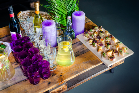 tea table: A carafe of fruity beverage with rosemary and lemon and wooden tray of appetizers at a banquet on a decorated tea table. Beautifully decorated table set  in the restaurant Stock Photo