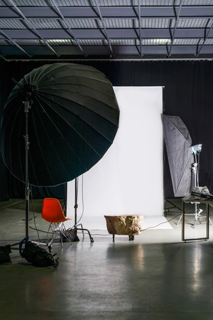 interior lighting: Empty photo studio with modern interior and lighting equipment. Preparation for studio shooting: empty chair and studio lighting Stock Photo