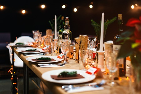 Decorated Christmas holiday table ready for dinner. Beautifully decorated table set with candles, spruce twigs, plates and serviettes for event in the restaurant