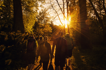 Group of friends walking with backpacks in sunset from back. Adventure, travel, tourism, hike and people friendship concept