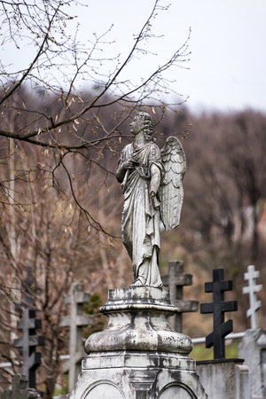 stone tombstone: Old tombstone sculpture of an angel with broken arm and wings on the cemetery Stock Photo