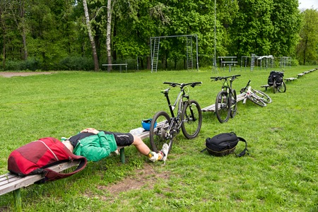 helmet seat: Cyclist resting on a bench in the park. Tired young man with his mountain bike in the forest resting and making pause