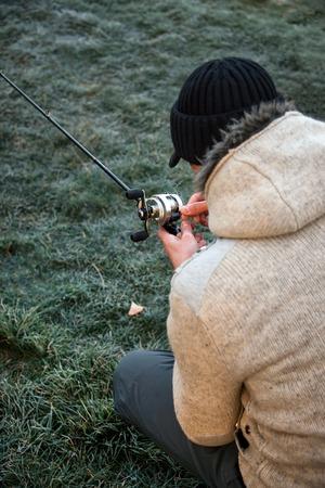 untangle: Fisherman sitting on ground and untangle fishing line