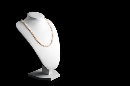 perlas: Collar de perlas naturales en un soporte sobre fondo negro. mujeres accesorios de lujo Foto de archivo