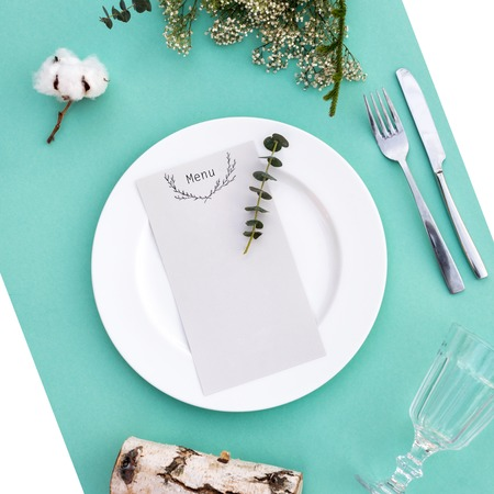 romantic places: Dinner menu for a wedding or luxury evening meal. Table setting from above. Elegant empty plate, cutlery, glass and flowers.