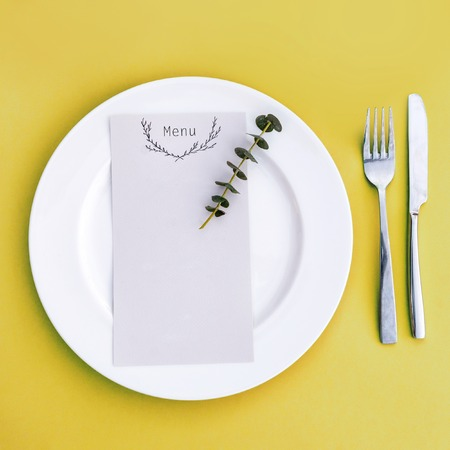 Dinner menu for a wedding or luxury evening meal. Table setting from above. Elegant empty plate, cutlery and flowers Archivio Fotografico