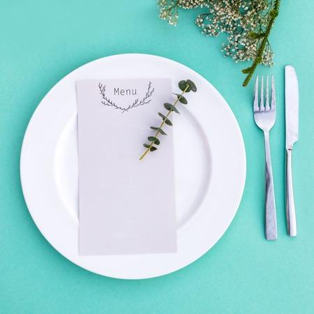 Diner menu voor een huwelijk of een luxe diner. Tabel omgeving van bovenaf. Elegant leeg bord, bestek en bloemen