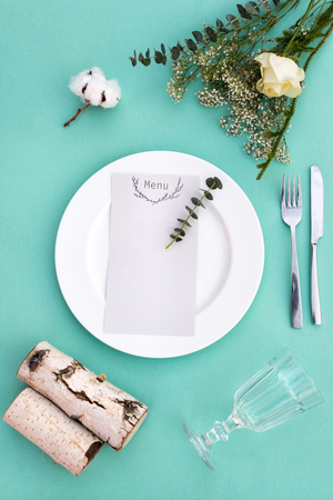 Dinner menu for a wedding or luxury evening meal. Table setting from above. Elegant empty plate, cutlery, glass and flowers.