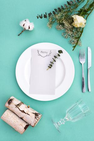 Dinner-Menü für eine Hochzeit oder ein Luxus-Abendessen. Tabelleneinstellung von oben. Elegante leeren Teller, Besteck, Glas und Blumen.