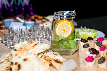 cruda: Colorful Traditional Mexican appetizers: various fajitas, nachos,  salsa cruda served on a beautifully decorated table. Guacamole with avocado, lime, tomato, and cilantro with tortilla chips Stock Photo