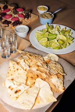 cruda: Colorful Traditional Mexican appetizers: various fajitas, nachos,  salsa cruda served on a beautifully decorated table. Guacamole with avocado, lime Stock Photo