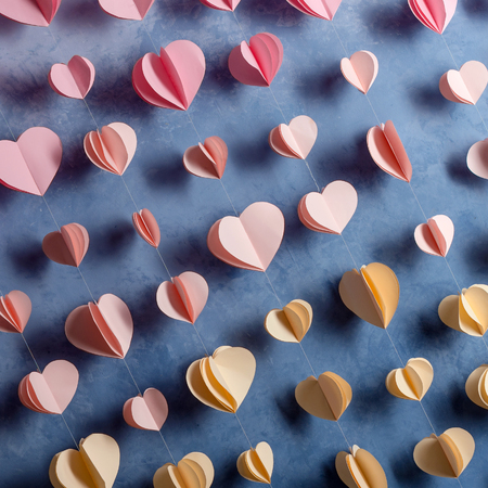 Colorful hearts paper garland hanging on the wall. Romantic Valentines day background