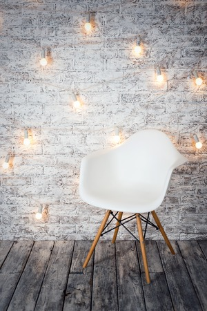 Empty white chair against the backdrop of a brick wall with a garland of light bulbs